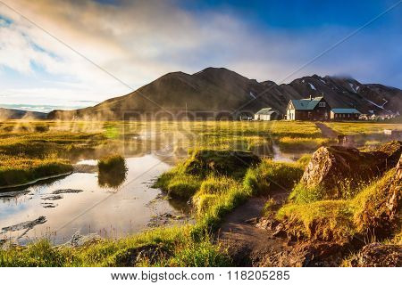 Sunrise Park Landmannalaugar. Above the source of thermal water steam rises. White nights in Iceland