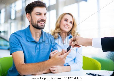 Photo of young male consultant and couple. Young woman and man buying new car in auto show. Buyer receiving keys. Focus on keys