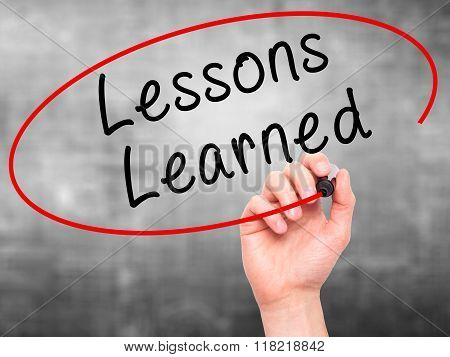 Man Hand Writing Lessons Learned With Black Marker On Visual Screen