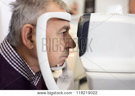 Close up of man in year look in apparatus for eyesight at eye doctor