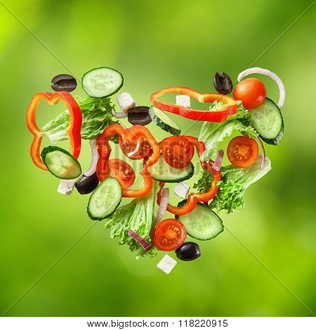 flying salad isolated on green background. Greek salad: red tomatoes, pepper, cheese, lettuce, cucumber and olives