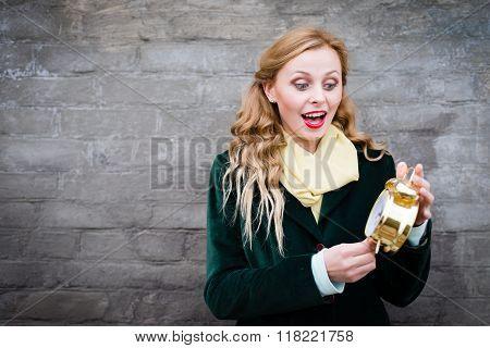Pretty girl with golden alarm clock