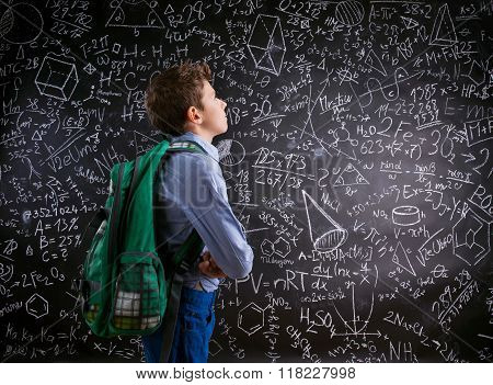 Boy  with schoolbag against big blackboard with mathematical sym