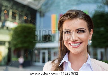 Detail of smiling businesswoman against glassy modern office bui