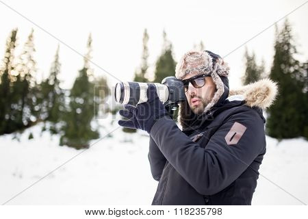 Man with professional camera photographing the mountain.Taking a photo of a mountain landscape