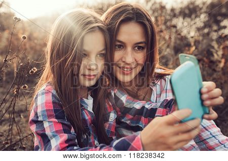happy mother and daughter making selfie outdoor in summer. Happy family spending summer vacation tog