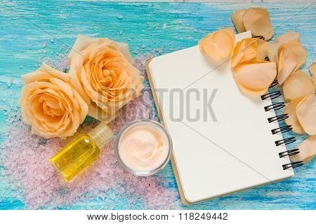 cosmetic products from rose cream and a bottle of rose water essential oil flowers on turquoise wooden background notebook mockup place for text