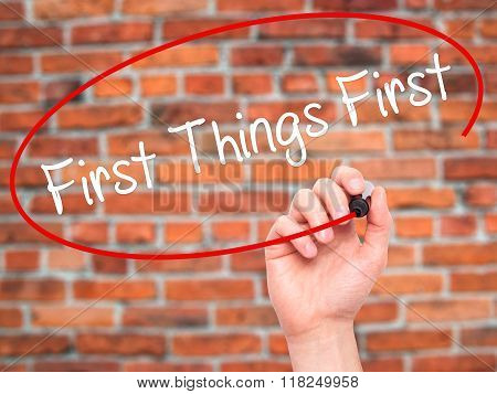 Man Hand Writing First Things First With Black Marker On Visual Screen