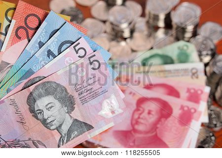 Assortment Of Australian Dollar Bank Notes On Front Of A Pile Of  Chinese Yuan