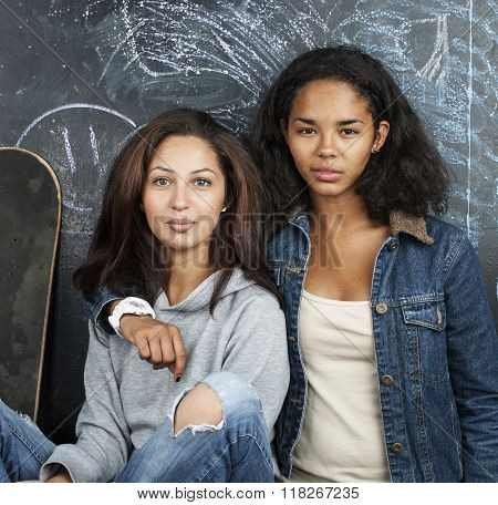 two mulatto girlfriends teenage in classroom hugging at blackboard, back to school concept