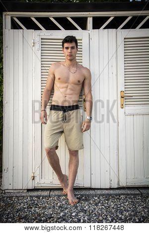 Young Man Standing in Doorway of Rustic Beach Hut