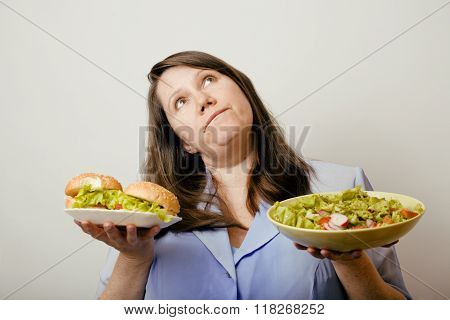 fat white woman having choice between hamburger and salad close up, unhealth fast food