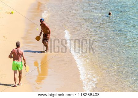 Tourists Playing Racket Ball At The Beach Of Ios Greek Island, In Cyclades.