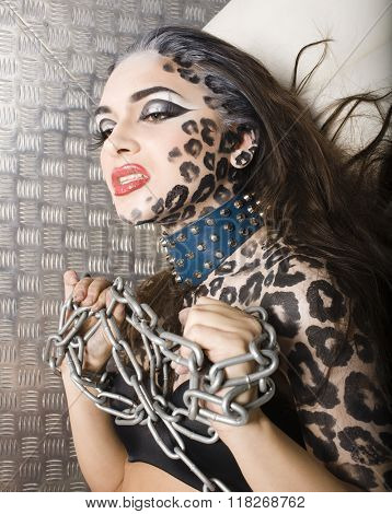 young sexy woman with leopard make up all over body, cat bodyart closeup in chains