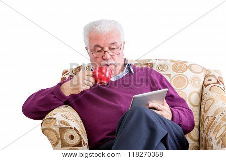 Man Sipping Coffee And Reading Tablet Computer