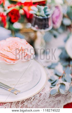 White wedding cake decorated with flowers on wooden background