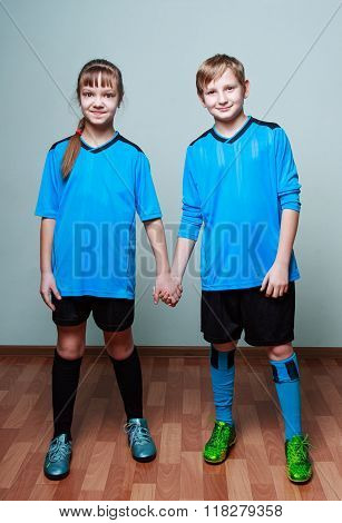 A Boy And A Girl In Blue Sporting Uniform Holding Hands