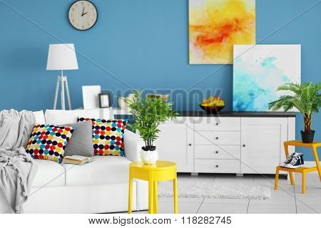 Living room interior with white furniture and green plants and pictures on blue wall background