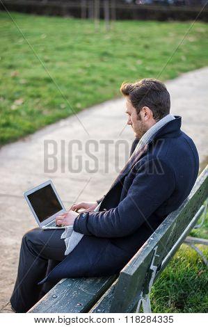 Handsome elegant businessman working in a park