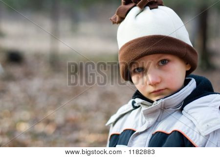 Picture or photo of serious crying young boy standing outside with a