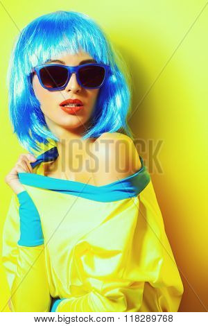 Bright glamorous girl in vivid clothes and a wig alluring over green background. Beauty, fashion. Cosmetics, hairtsyle. Optics, eyewear.