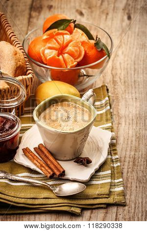 Fragrant coffee and fruits for breakfast. Tangerines. Lemon and sweet jam on wooden board in rustic style