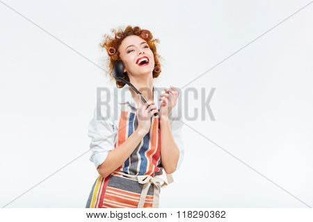 Laughing redhead housewife with curly hair in apron posing with soup ladle isolated on a white background