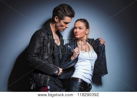 punk young man is looking at his girlfriend while takes off her jeather jacket in studio background