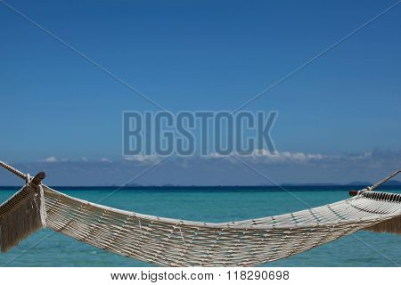 Empty hammock on beach ober blue sea background