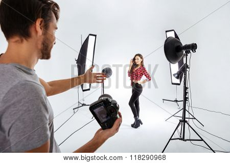 Photographer shooting model in studio with softboxes