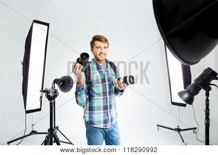 Happy male photographer standing in photo studio with equipments