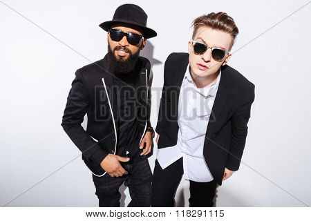 Two serious young men standing and staring on you over white background