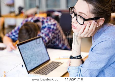 Tired young woman in glasses with laptop sitting in meeting room while her colleague sleeping on the table