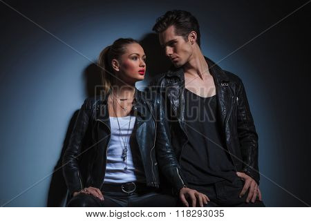 sexy couple in leather pose in dark studio background, man lean on the wall looking at the woman and she pose looking away