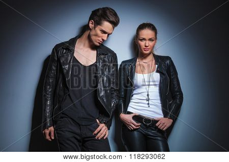 young rocker looking down with hand in pocket while his girlfriend pose in her leather jacket with hands on waist in studio background