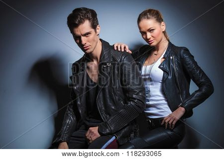 attractive young woman in leather jacket holding her boyfriend while touching his shoulder, both looking at the camera.