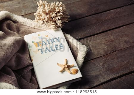 A book, seashells, stony corals and a soft blanket on wooden background