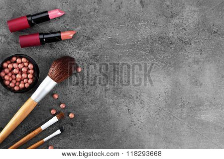 Make-up brushes, lipsticks, and blusher, on grey background