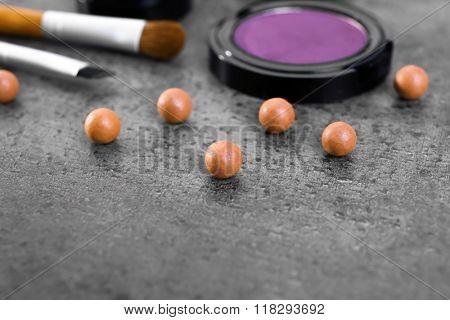 Make-up brush, eye-shadow and blusher balls, on grey background