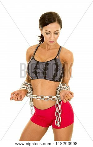 Woman In Sports Bra And Short Chain Around Wrists Look Down