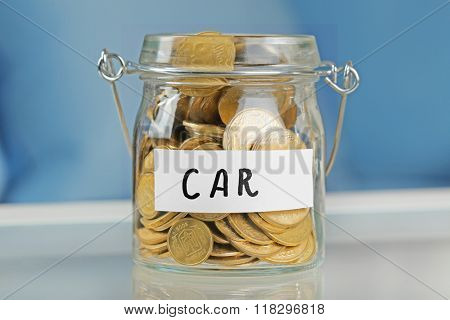 Glass jars with Ukrainian coins for car on a table