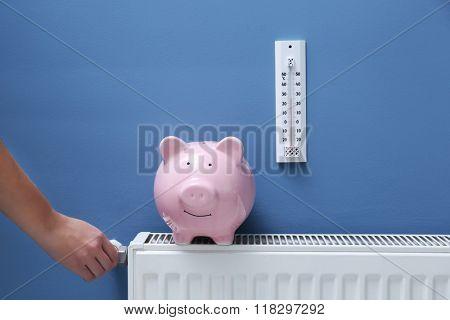 Hand adjusting the temperature on radiator. Saving  heating in winter