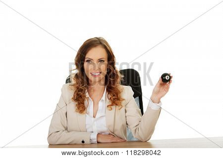 Businesswoman holding eight billiard ball.