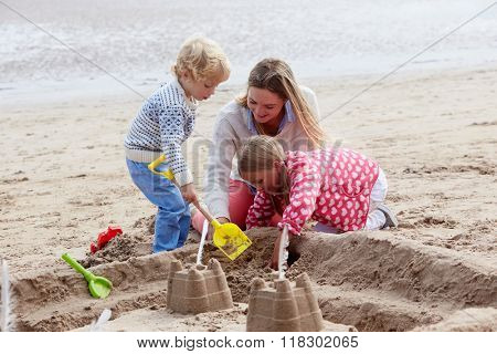 Mother And Children Building Sandcastles On Beach Together
