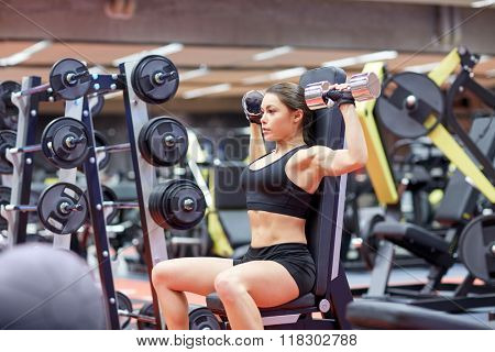sport, fitness, bodybuilding, weightlifting and people concept - young woman with dumbbell flexing muscles in gym from back