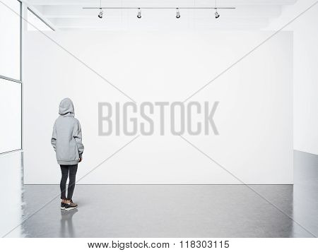 Young woman walking in modern gallery and looking at the blank canvas