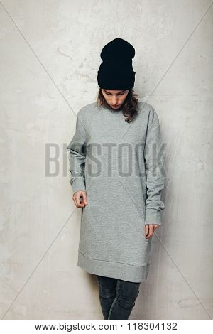 Young girl wearing blank and oversize long hoody. Concrete wall background. Vertical