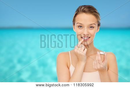 beauty, people and lip care concept - smiling young woman applying lip balm to her lips over blue sea and sky background