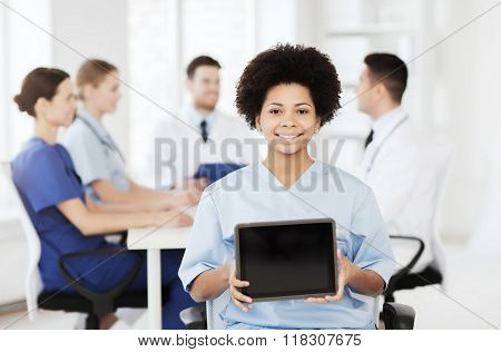 clinic, profession, people and medicine concept - happy female doctor or nurse showing tablet pc computer blank screen over group of medics meeting at hospital