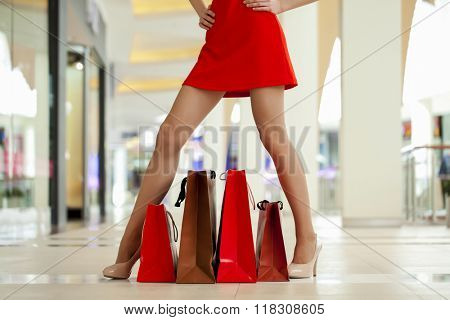Legs of shopaholic wearing red dress while carrying several paperbags